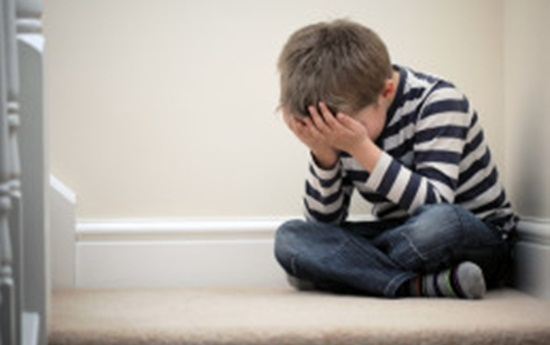 Upset problem child sitting on staircase